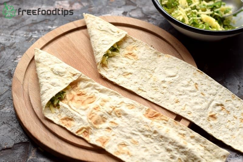 Start folding flatbread strips in the shape of triangle