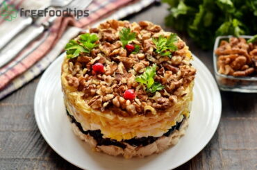 Layered chicken salad with prunes and walnuts